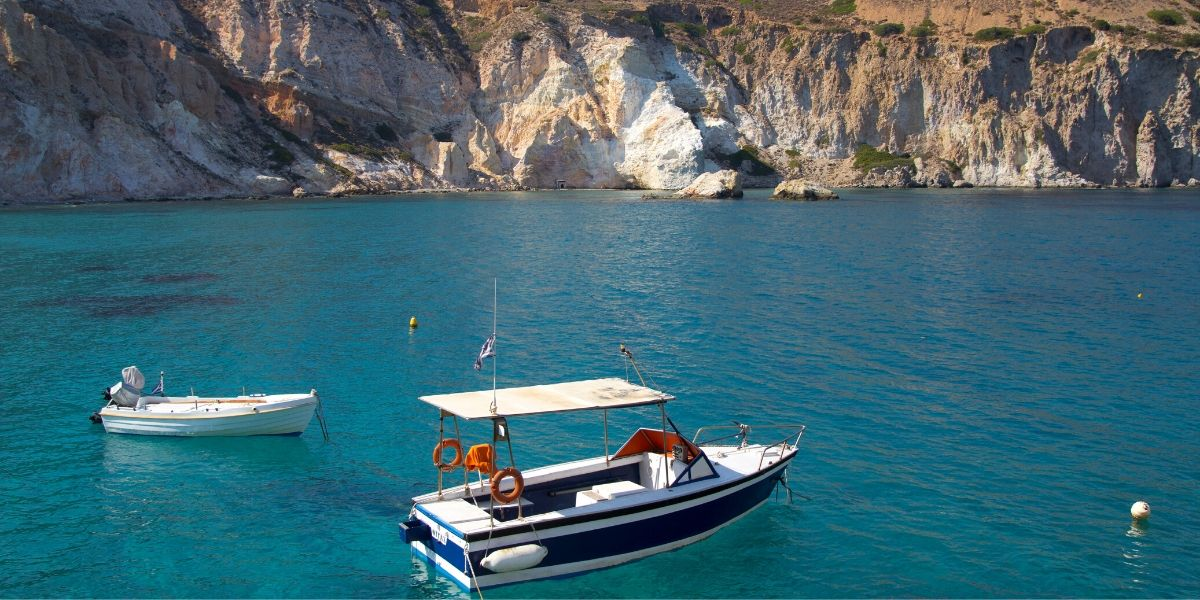 boats, turquoise waters, rock