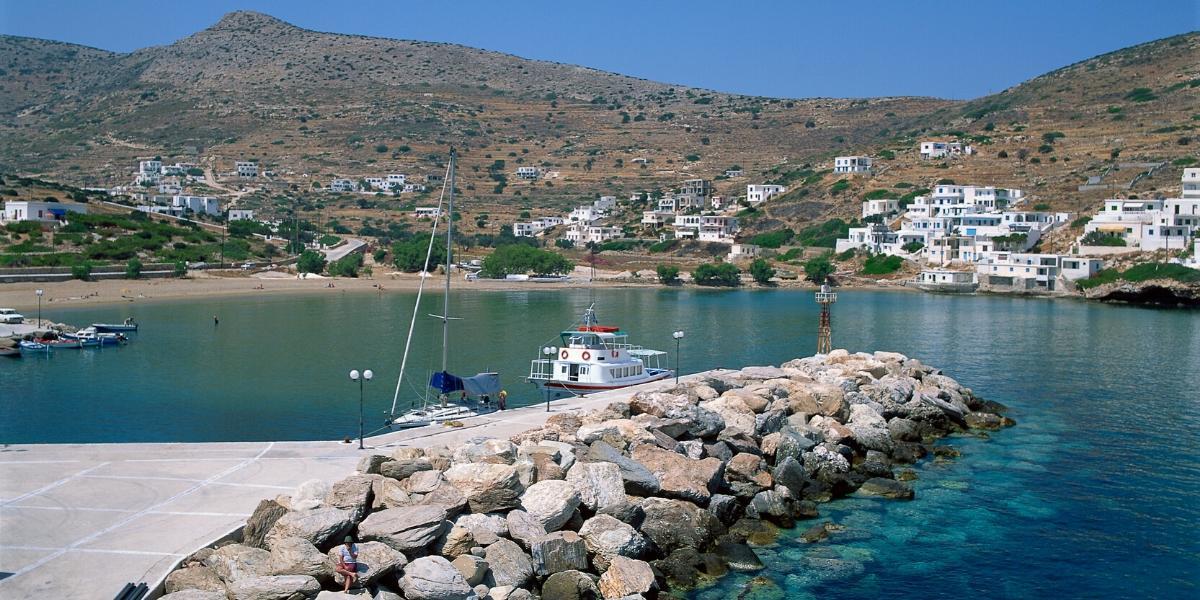 λιμάνι, κυματοθράυστης με πέτρες, άσπρα κτήρια, βάρκες, καθαρά νερά