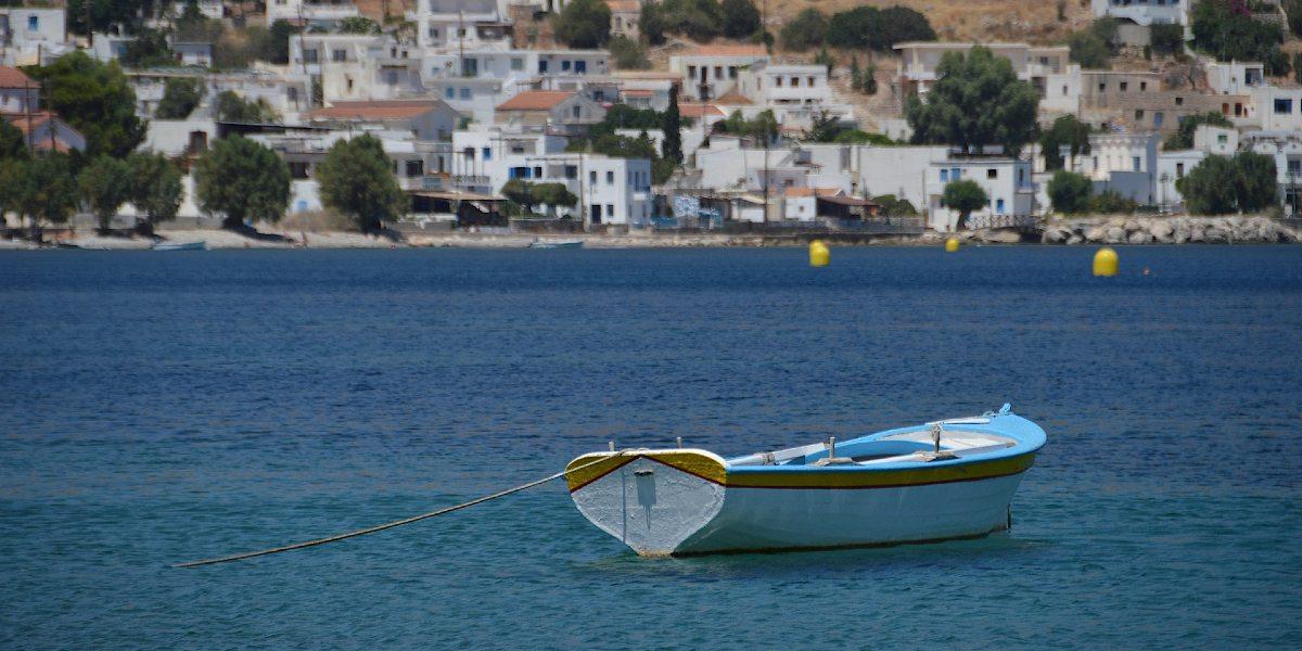 γαλάζια και άσπρη βάρκα, μπλε θάλασσα στη Χάλκη, άσπρα σπίτια
