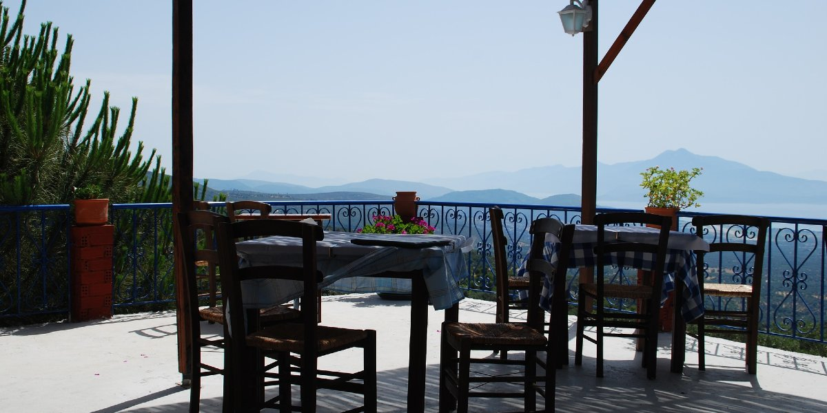 balcony overlooking Samos, tables with chairs, tavern, plants