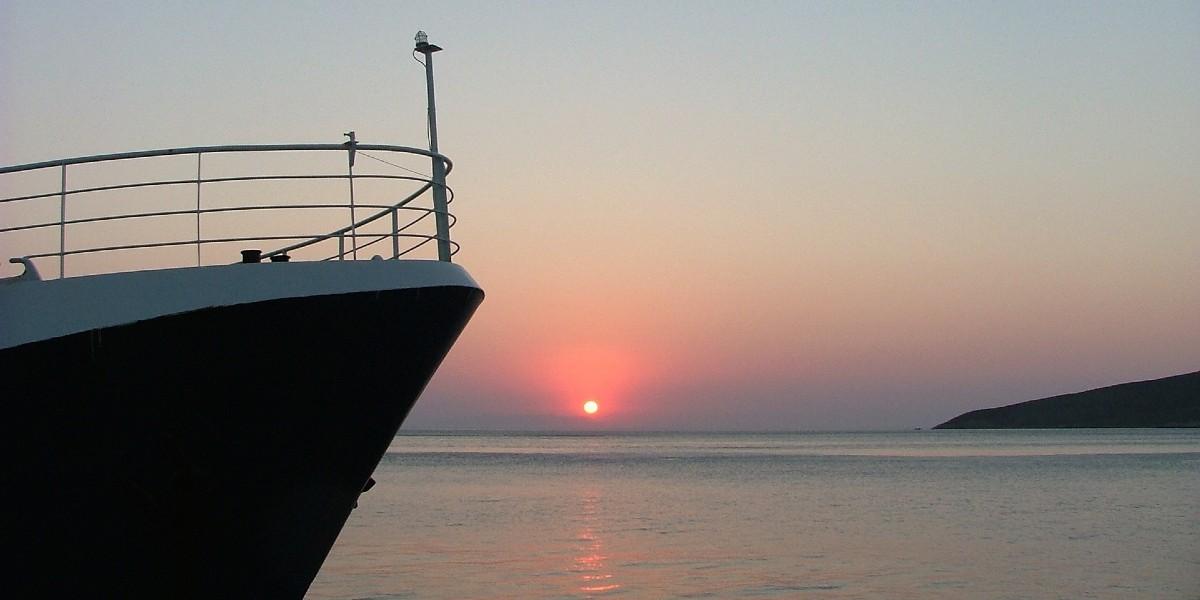 ροζ και μωβ ουρανός από το ηλιοβασίλεμα, πλώρη πλοίου κοντά στην Τήλο