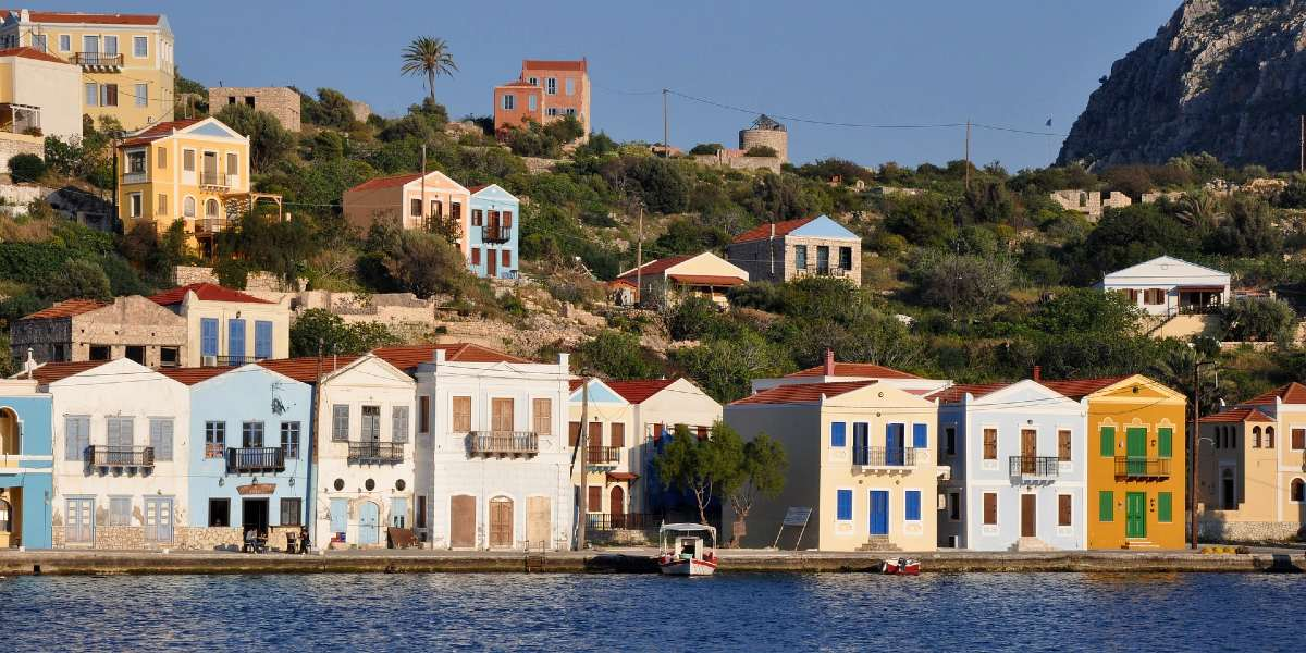 Colorful houses in Kastellorizo, port, palm tree, fishing boat, sea, Dodecanese
