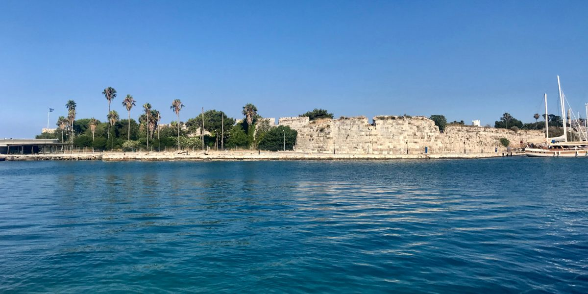 Castle, palm trees, coastal road, sailboats, Kos port