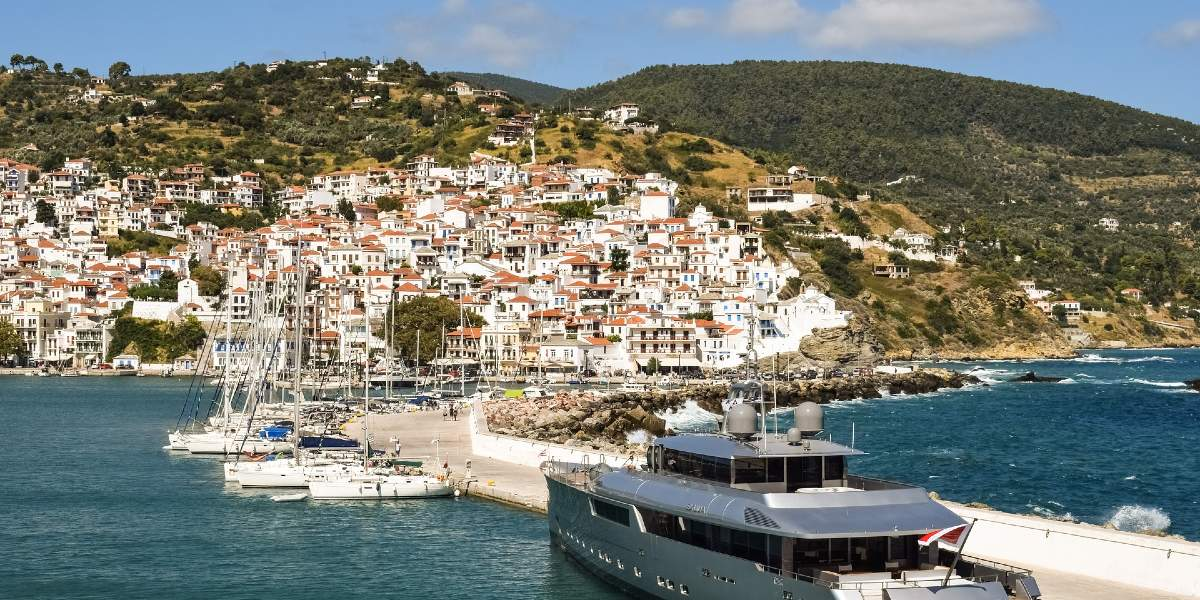 port in Skopelos, pier, gray speedboat, sailing boats, white buildings, green nature and mountains