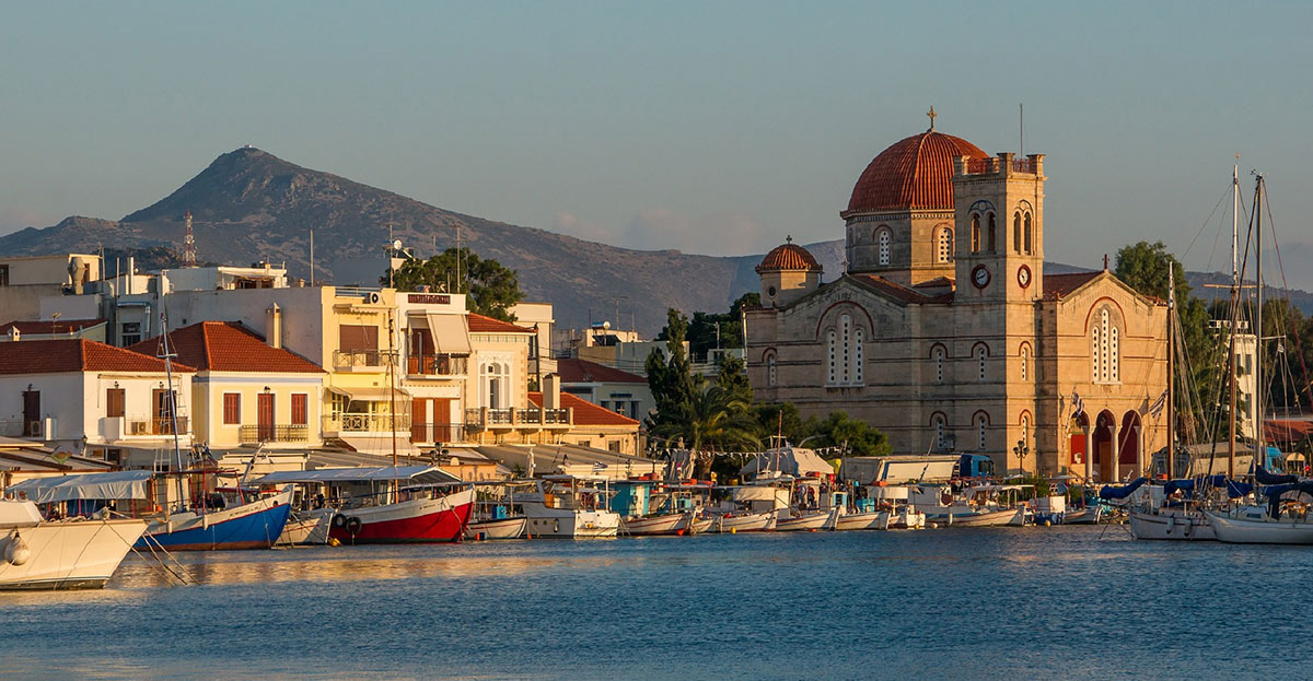 Church, shops, sailing boats at the port of Aegina, sunset colours, Saronic Gulf, ferry routes from Piraeus