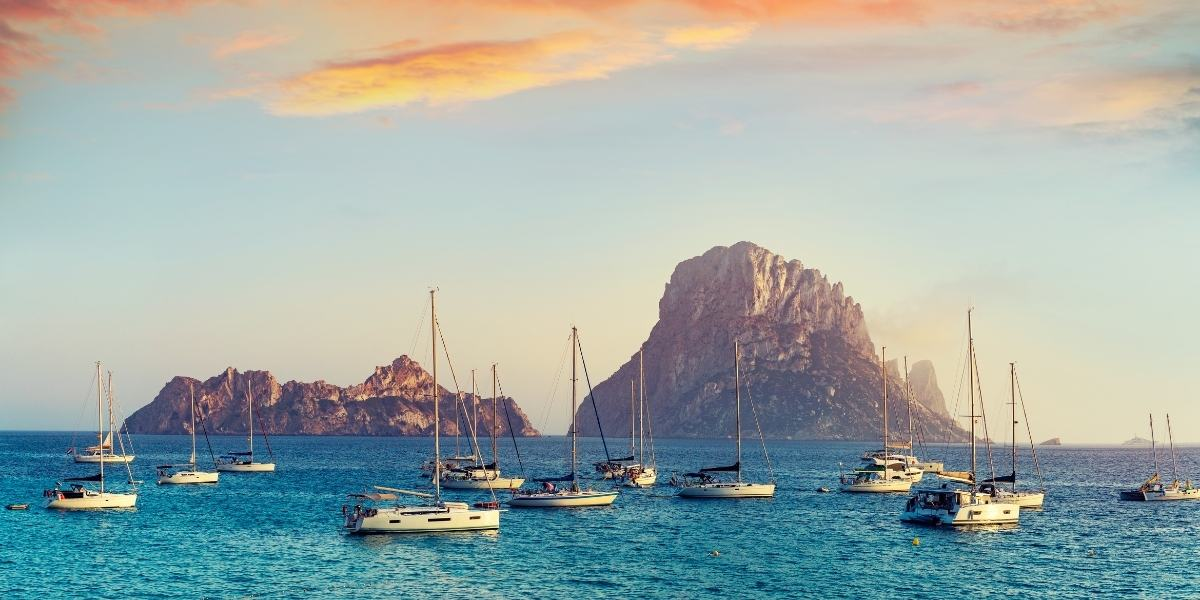 Sailing boats in Cala d'Hort with a view of the Es Vedra islet in Ibiza
