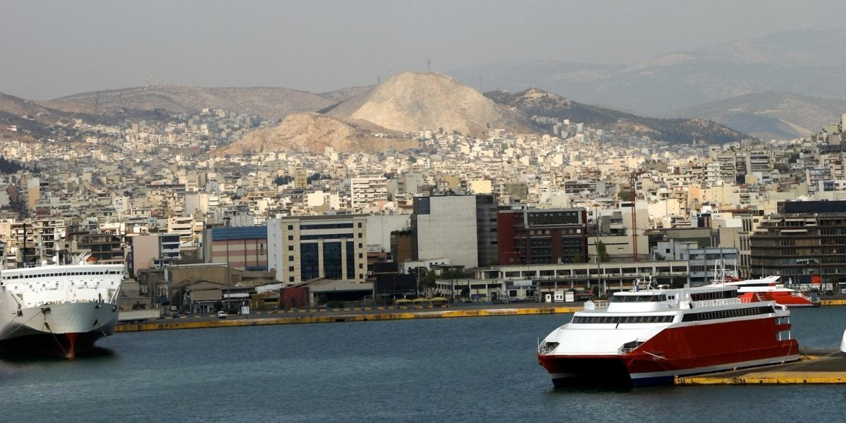 Ferries at the port of Piraeus in Athens, departure platforms, buildings, cityscape, mountain