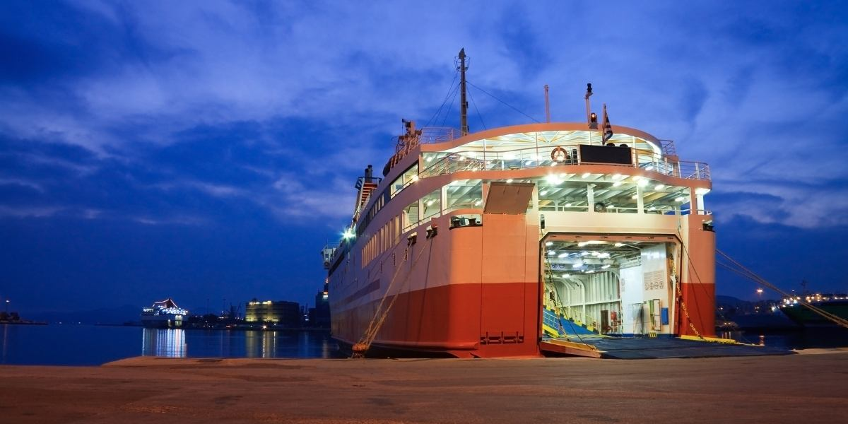 Ferry with open doors at the port of Piraeus, night sky, sea reflections