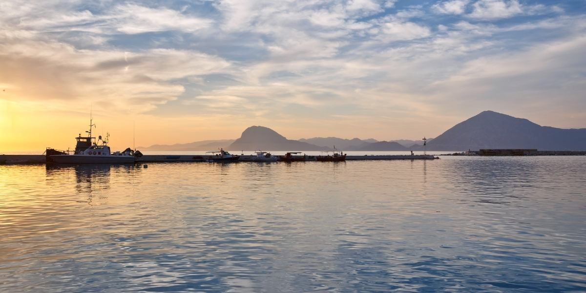 Fishing boat at the port of Patras, sunset hour, clouds, mountains, Peloponnese, port entry