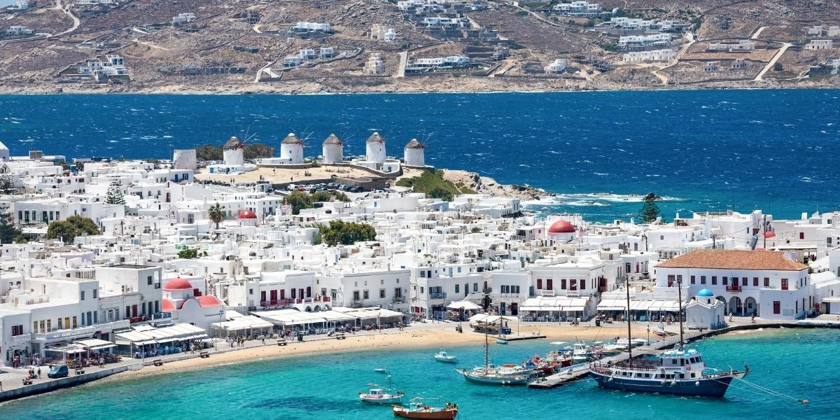 The old port of Mykonos, boats, white houses, windmills, waves, blue sea