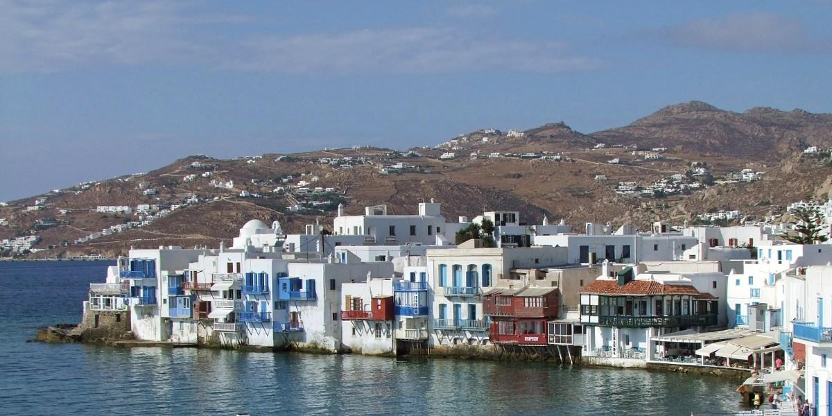 Il vecchio porto e la città di Mykonos, la tradizionale architettura cicladica, le rotte dei traghetti da Atene