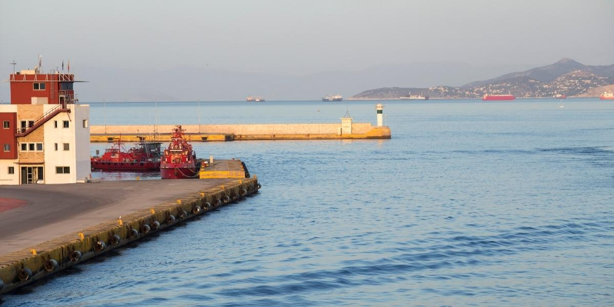 Sunset hour at the port of Piraeus, lighthouse, ferries, dock