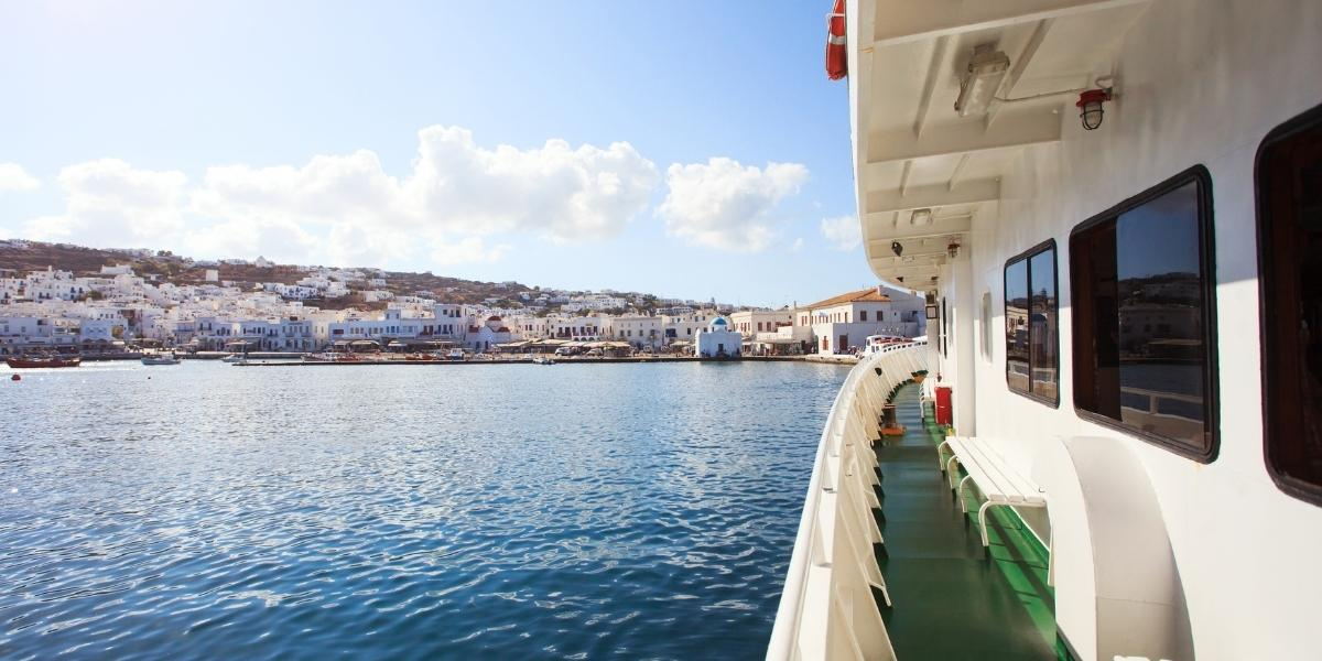 Ferry arriving at the port of Mykonos, island, houses, blue sea, clouds, ferry deck