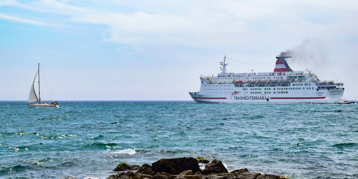 A sailing boat and a ferry of the Trasmed company outside the port of Almería, south Spain, ferry routes from the north of Africa and ferry tickets
