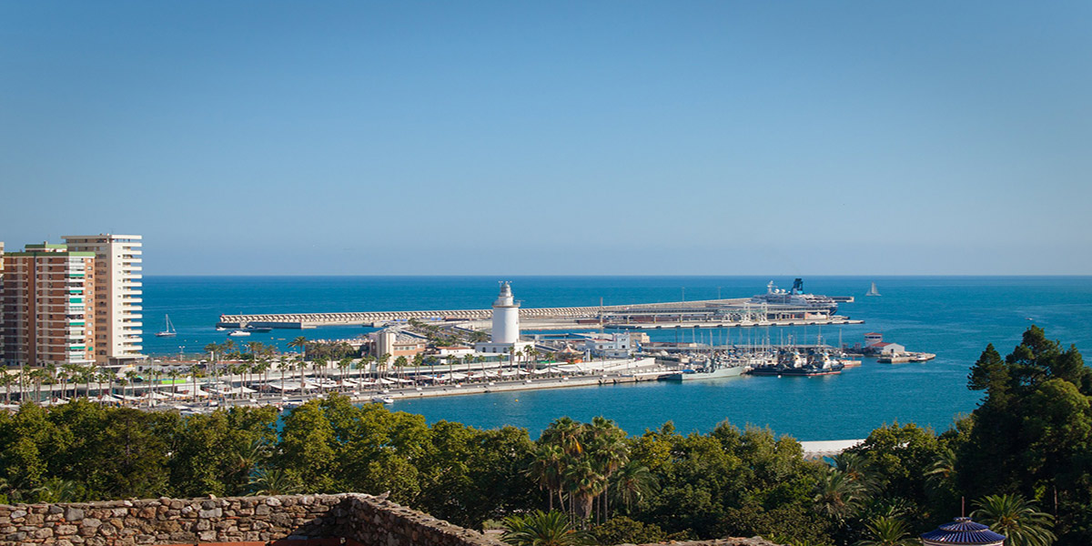 View of the port of Malaga, lighthouse, buildings, ferries and cruise ships, palm trees, holidays and ferry tickets