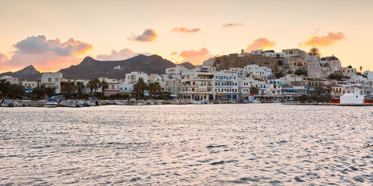 The town and port of Naxos in sunset hour, clouds, pink sky, houses, castle