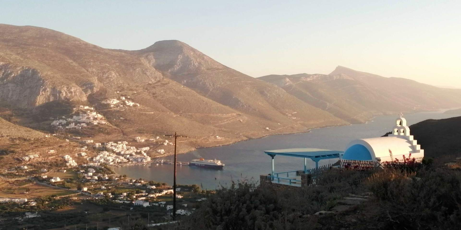 Ferry departing from the port of Aigiali in Amorgos, view of the port from Tholaria village
