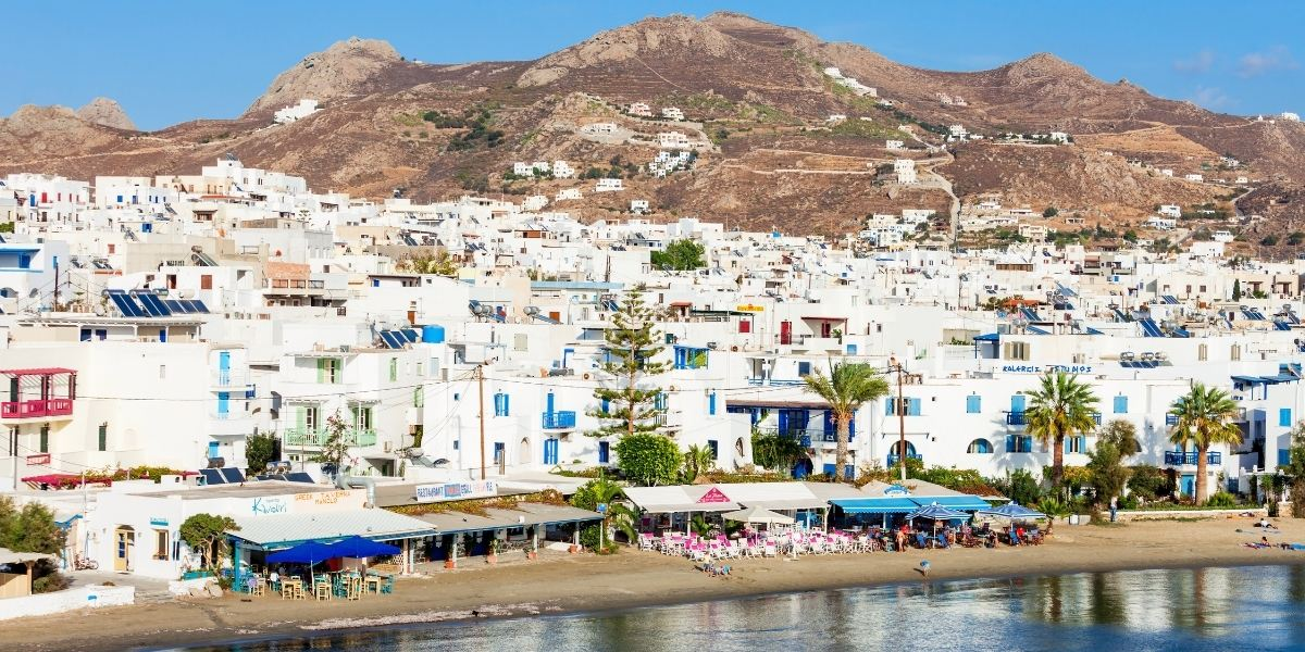 The beach of Agios Georgios, close to the port of Naxos, white houses, shops, hill, island
