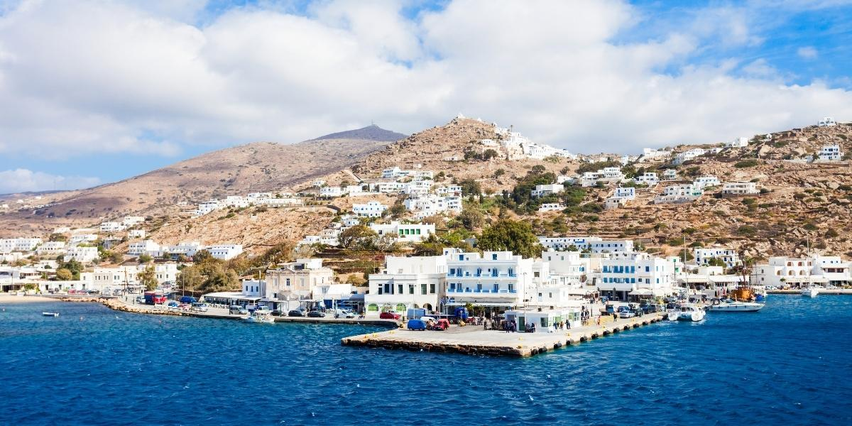 Main ferry platform at the port of Ios, cars, white houses, blue sea, island