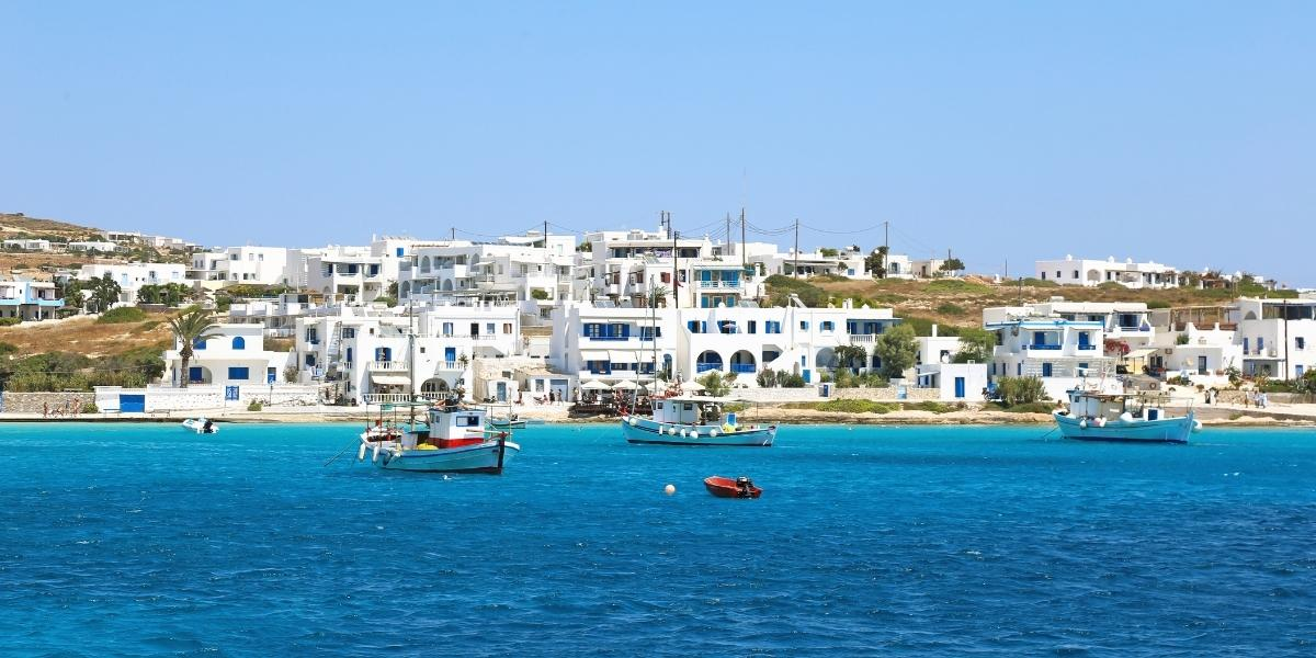 Fishing boats at the port of Ano Koufonisi, white houses, small island, crystal blue sea