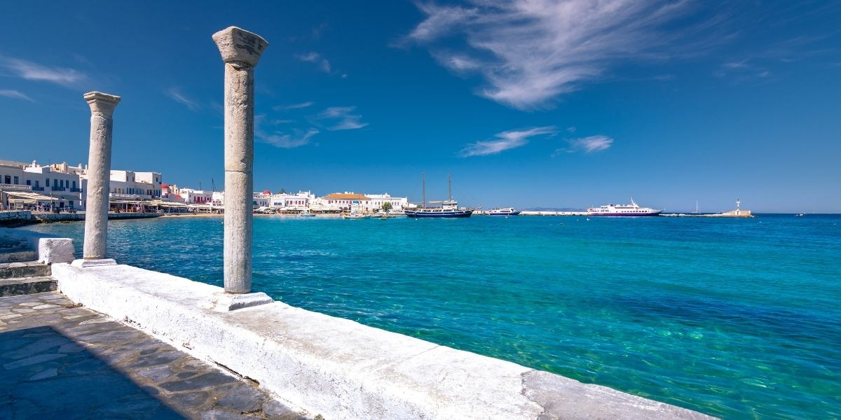The old port of Mykonos, fishing boats, ancient columns, pavement, blue sea,