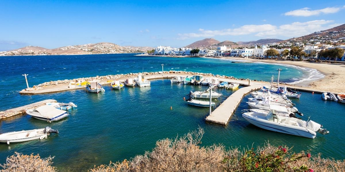 Marina, fishing boats and cruise boats, Paroikia port, Paros, blue sea, beach