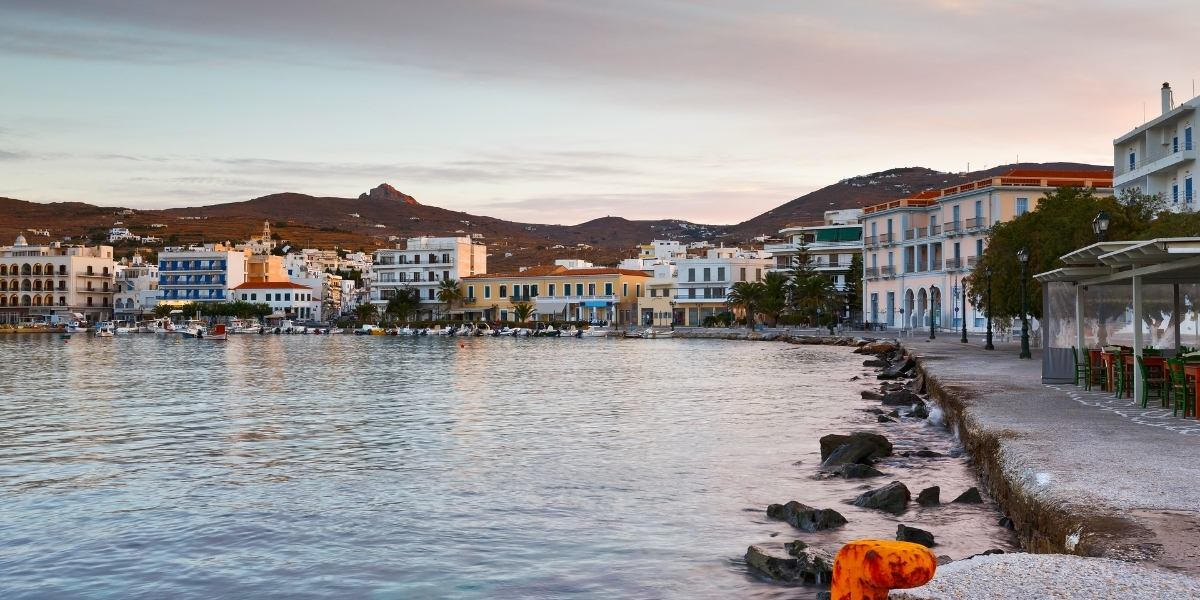 Sunset hour at the port of Tinos, shops and buildings by the sea, mountains and cloudy sky
