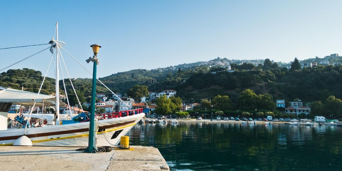 The port of Glossa in Skopelos, fishing and sailing boats, forest, ferry platform