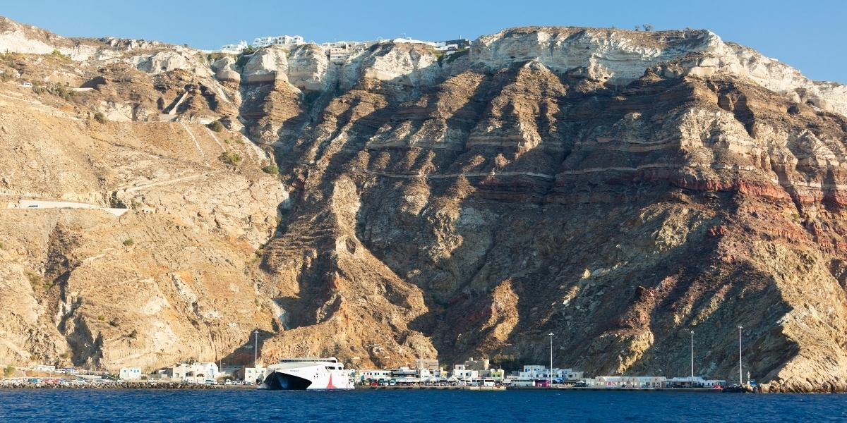 The port of Athinios in Santorini, boats and ferry, volcanic rock, cliff, village