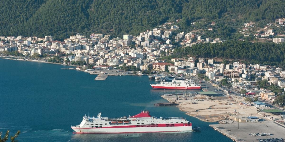 Ferries arriving and departing at the port of Igoumenitsa, coastal town, forest, calm sea