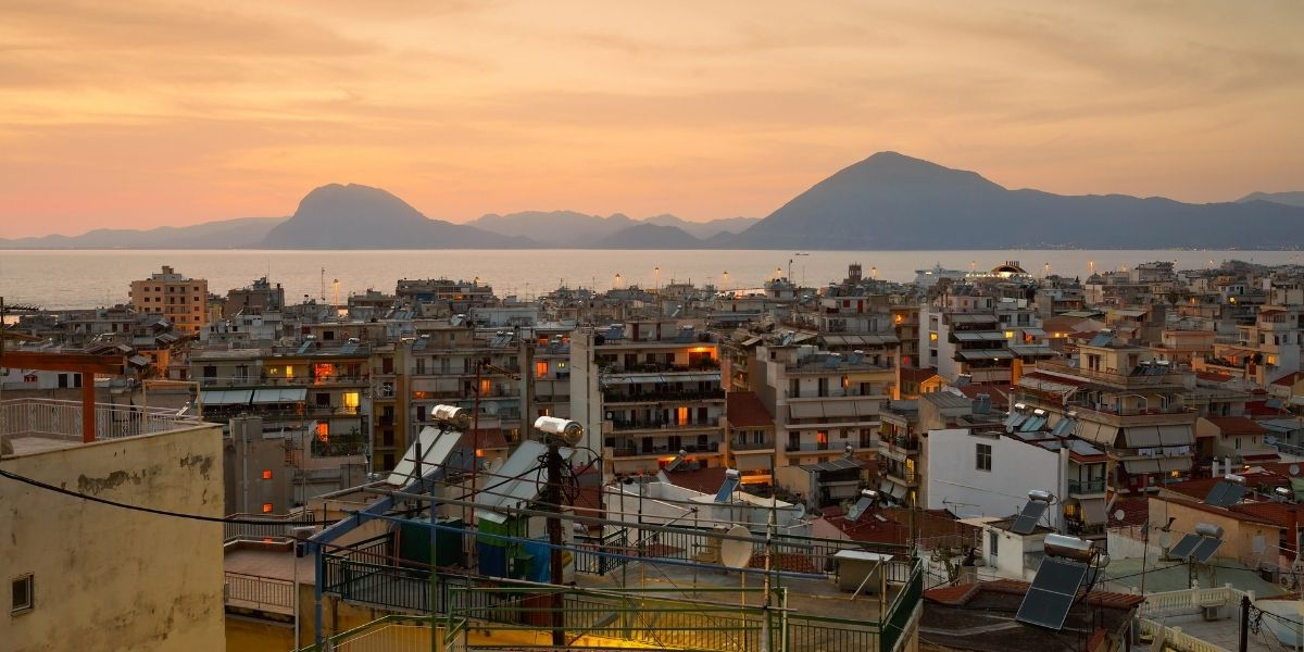The city of Patras after sunset, orange sky, city lights, houses, mountains