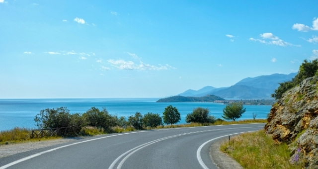 road in the Peloponnese, sea view, blue sky, mountains, clouds, trees