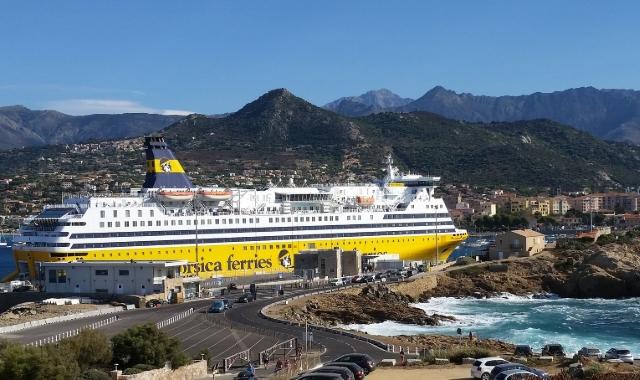 Traghetto giallo, bianco e blu dei traghetti Corsica in un porto della Sardegna - rotte da e per la Corsica