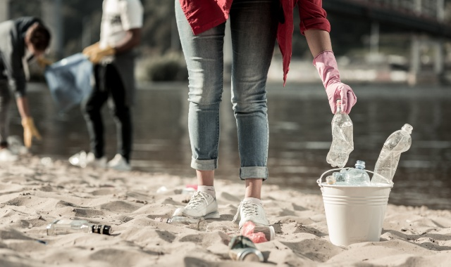 beach cleaning, plastic bottles, garbage cans, woman in jeans, protection of the environment