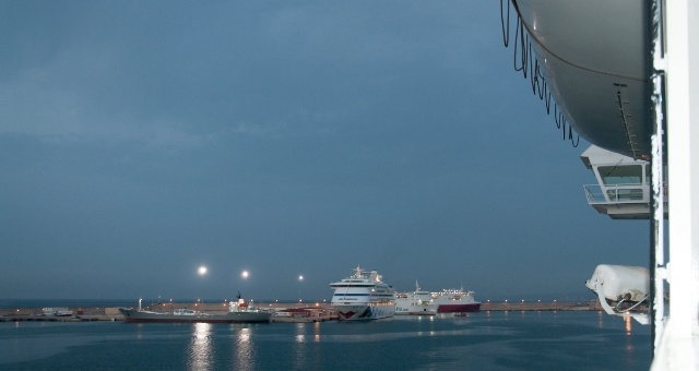 Ferry arrives at the port of Palma de Mallorca, early morning, lights, cloudy sky