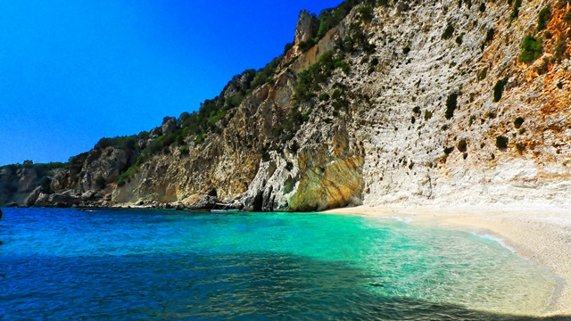 sandy beach in Ithaca, hill cliff, vacations in the Ionian islands, cheap ferry tickets