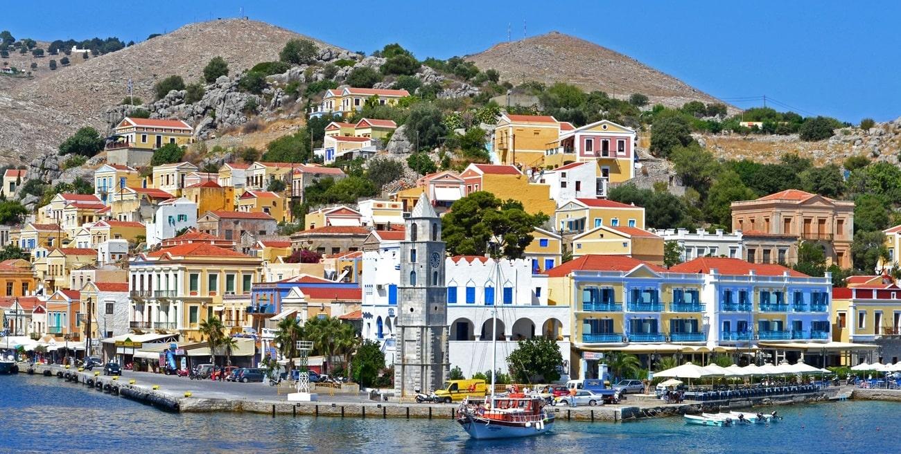Λιμάνι της Σύμης,  πολύχρωμα νεοκλασικά σπίτια, πλαγιά λόφου, βράχια, καμπαναριό