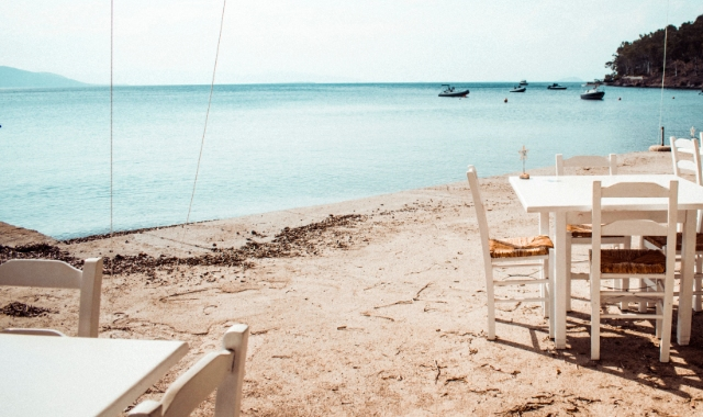 Tavern tables and chairs on a beach in Aegina