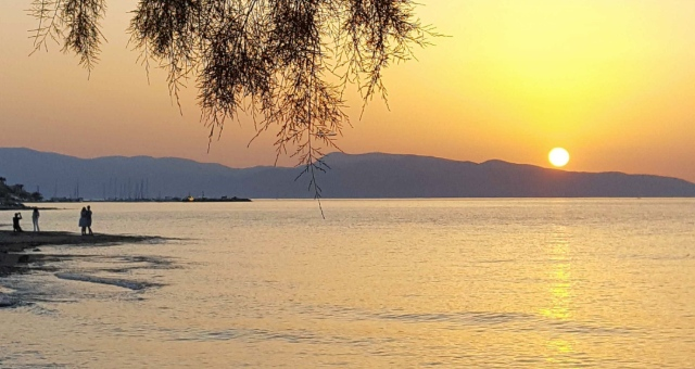 Sunset colours and sea reflection at a beach in Agistri, Saronic Gulf, ferry routes from Piraeus