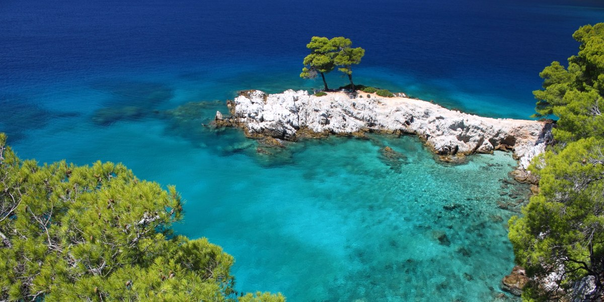 Crystal blue sea, trees and nature in Alonissos, Sporades islands, ferry routes and tickets