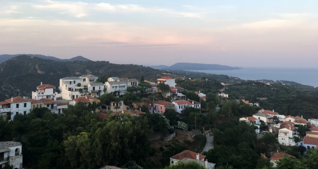 view of a village in Alonissos, white buildings, green trees, sunset