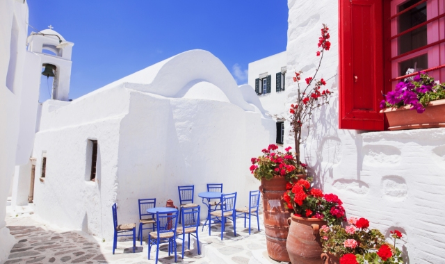 white church in Amorgos, red window and flowers, blue chars, ferryhopper