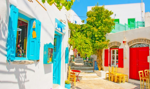 white houses with blue and red windows, traditional street in Amorgos, ferry tickets