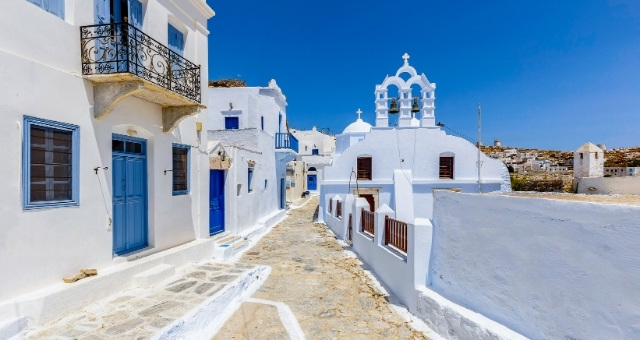 Small alley in the Chora of Amorgos, white houses, blue windows, church, balconies