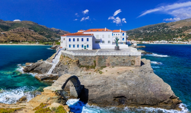 The impressive Chora of Andros, statue, traditional architecture, blue sea, sky, ferry routes Cyclades