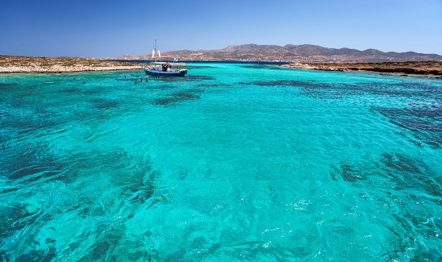 Fishing boat sailing on turquoise waters in Antiparos