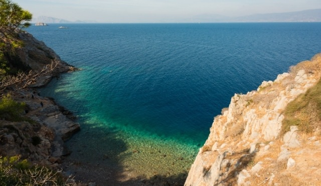 Avlaki beach in Hydra with rocks and emerald waters