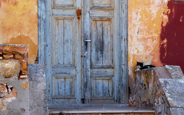 Colourful building, old doorstep, cat, Hydra architecture, history, holidays in the Saronic Gulf, ferry tickets from Piraeus