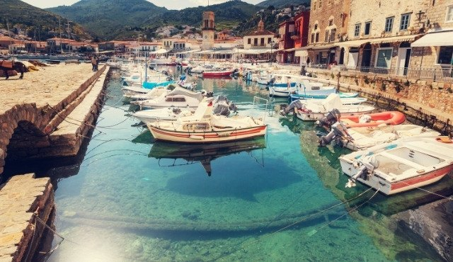 Quaint harbor in Hydra with clear waters and small boats