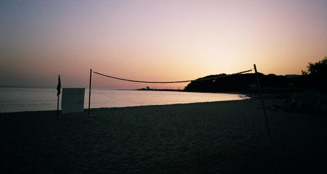Ξημέρωμα στην παραλία Μεσακτή, Ικαρία, άμμος, θάλασσα, ροζ ουρανός, δίχτυ βόλεϊ, σημαία, δέντρα